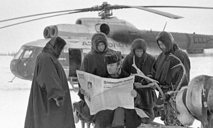 1979 год. оленеводы читают газету у вертолета, доставившего почту